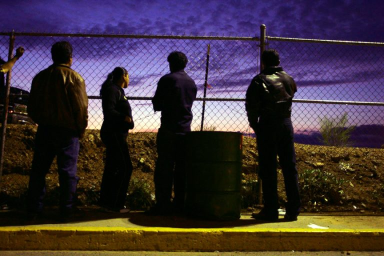Minutemen: America's Citizen Border WatchersNogales, Mexico- July 27, 2006A few migrants wait at the fence in Nogales Mexico. As night falls., many migrants who were returned to Mexico from the United States will try again to cross the border.The Minutemen are in the process of  putting up a fence between Mexico and United States about 70 miles from Nogales Mexico.